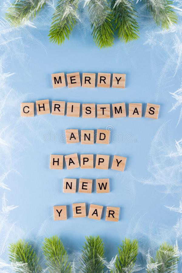 Merry Christmas and happy new year. Words from wooden letters on winter blue background. Template, greeting card. Holiday concept stock photos