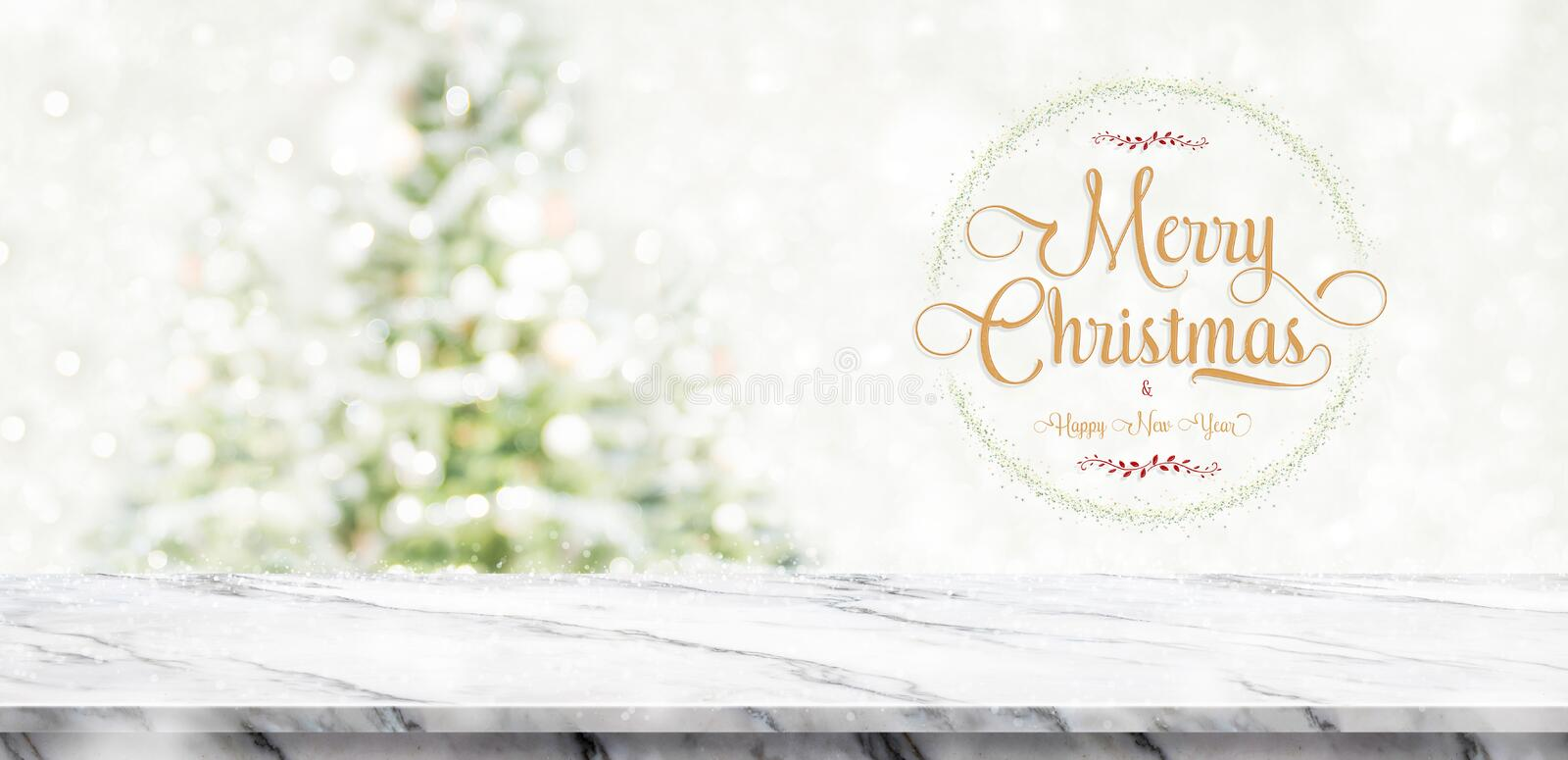 Merry Christmas and happy new year wreath with golden glitter te. Xture over white marble table top at blur bokeh christmas tree decor with string light royalty free stock images