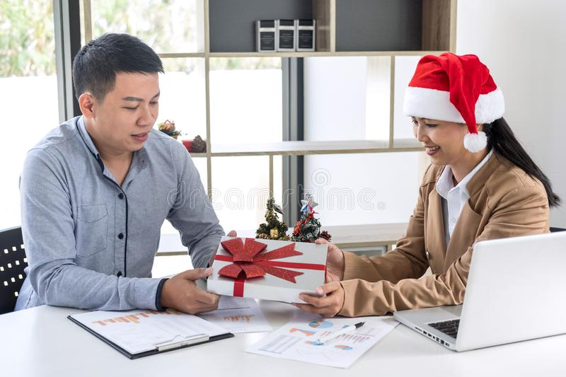 Merry Christmas and Happy New Year, Young business team are celebrating holiday in workplace are sitting in Santa hats and Give. A gift to the colleagues royalty free stock photography