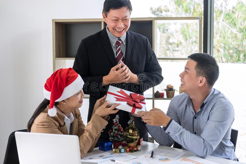 Merry Christmas and Happy New Year, Young business team are celebrating holiday in workplace are sitting in Santa hats and. Meeting party to Give a gift to the royalty free stock photos