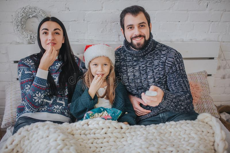 Merry Christmas and Happy New Year . Young family celebrating holiday at home. The Father is holding the remote from the. TV. Dad, daughter and mother are royalty free stock photography