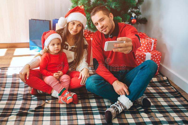 Merry Christmas and Happy New Year. Young man sits besides woman and child. He holds phone and takes selfie. Woman and stock photos