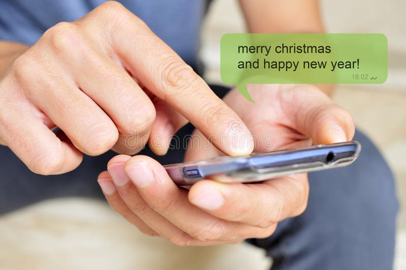 Merry christmas and happy new year. A young man with a smartphone and the text message merry christmas and happy new year in a chat bubble royalty free stock image