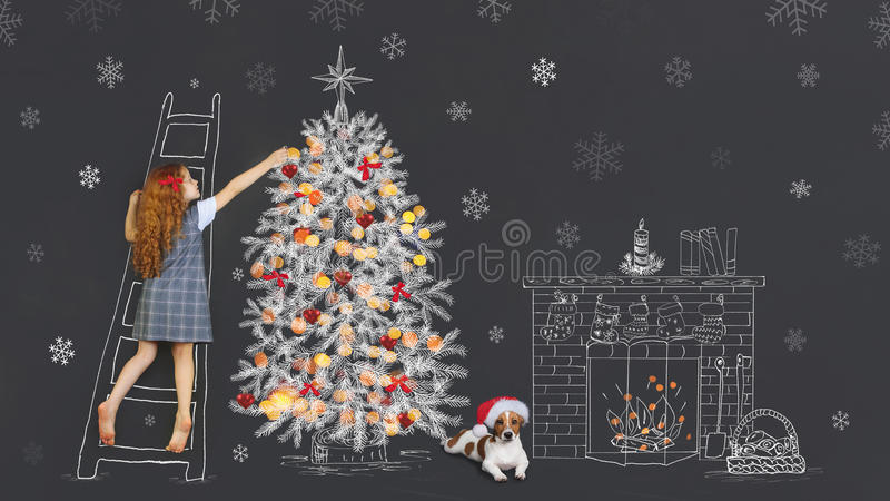 Merry christmas holiday for best friend. Little curly redhead girl and her puppy, decorate a fir tree drawing on chalkboard in the home. Merry Christmas, New royalty free stock photos