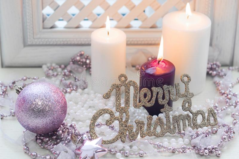 Merry christmas inscription, burning candles and delicate pink decorations royalty free stock photography