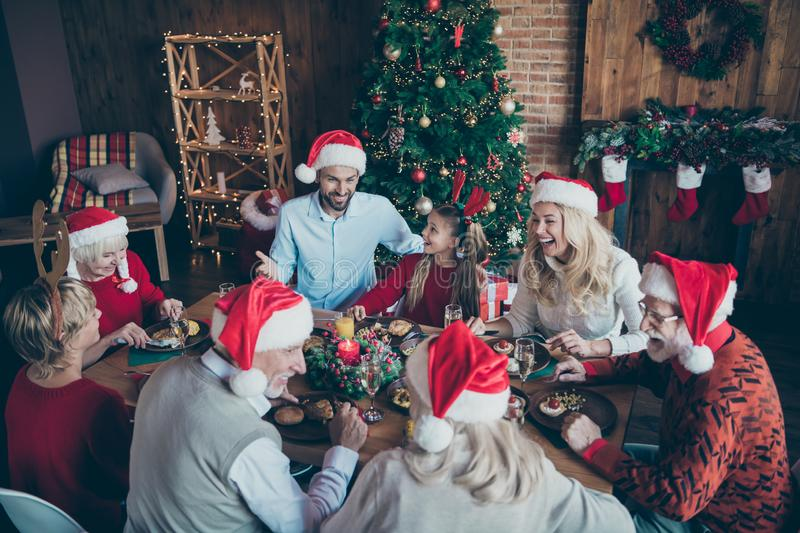 Merry christmas large family reunion gathering meeting sit table have x-mas feast father in santa claus hat cap joke royalty free stock image