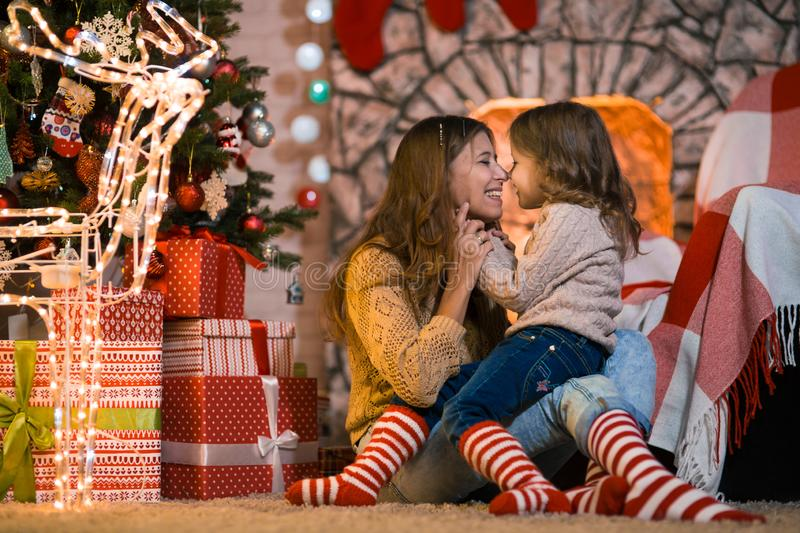 Little girl child at home by the fireplace with the family parent mother and Christmas tree with gifts and luminous garlands royalty free stock photography