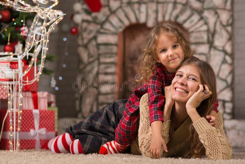 Little girl child at home by the fireplace with the family parent mother and Christmas tree with gifts and luminous garlands. Merry Christmas. Little girl child royalty free stock photos