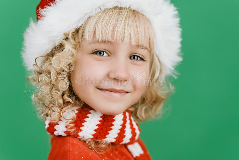 Merry Christmas Little girl in Santa hat on bright green vivid color background stock photography