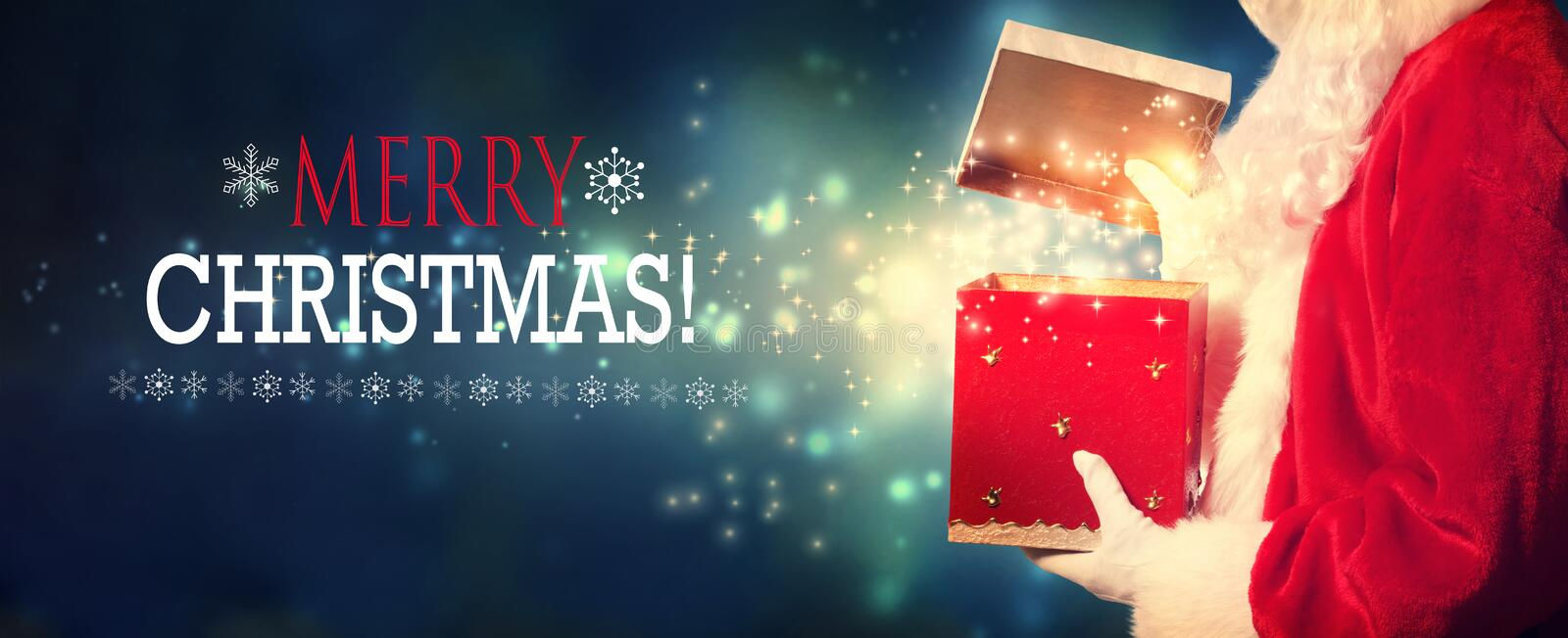 Merry Christmas message with Santa opening a gift box. On a shiny light background royalty free stock photography