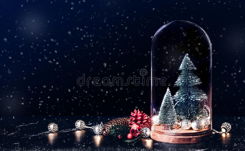 Merry Christmas with mistletoe and gift box icon with xmas tree. And glowing light string and pine cone decoration on marble table and blue background.Mock up stock photography