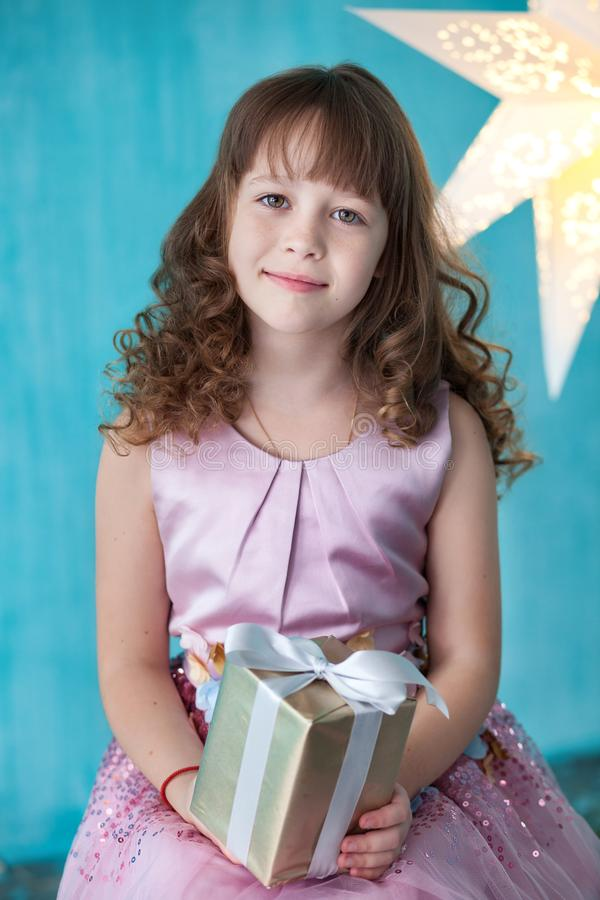 Merry Christmas! New Year 2020! Birthday gift. Happy little smiling girl with christmas gift box. Beautiful girl sits, enjoys Chri stock images