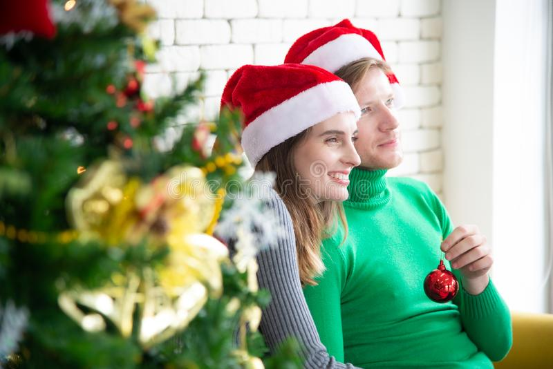 Merry Christmas and New Year concept. Young Caucasian lover with christmas theme clothing celebrate exchange presents each other. And talk with laugh and fun in royalty free stock photography