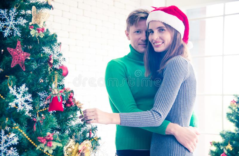 Merry Christmas and New Year concept. Young Caucasian lover with christmas theme clothing celebrate decorating chrismas tree. And talk with laugh love and fun stock photo
