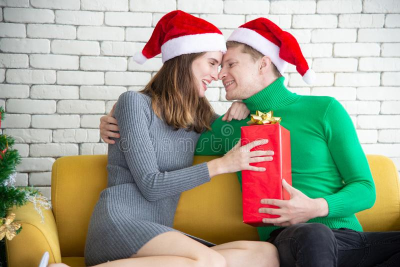 Merry Christmas and New Year concept. Young Caucasian lover with christmas theme clothing celebrate exchange presents each other. And talk with laugh and fun in stock photo