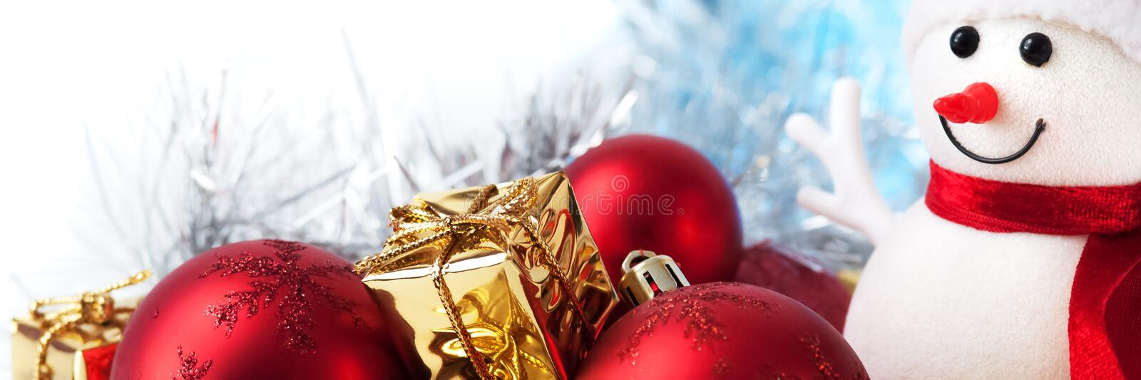 Merry Christmas, New Year, snowman, gifts in golden boxes and red balls on a blue and white bokeh background stock photography
