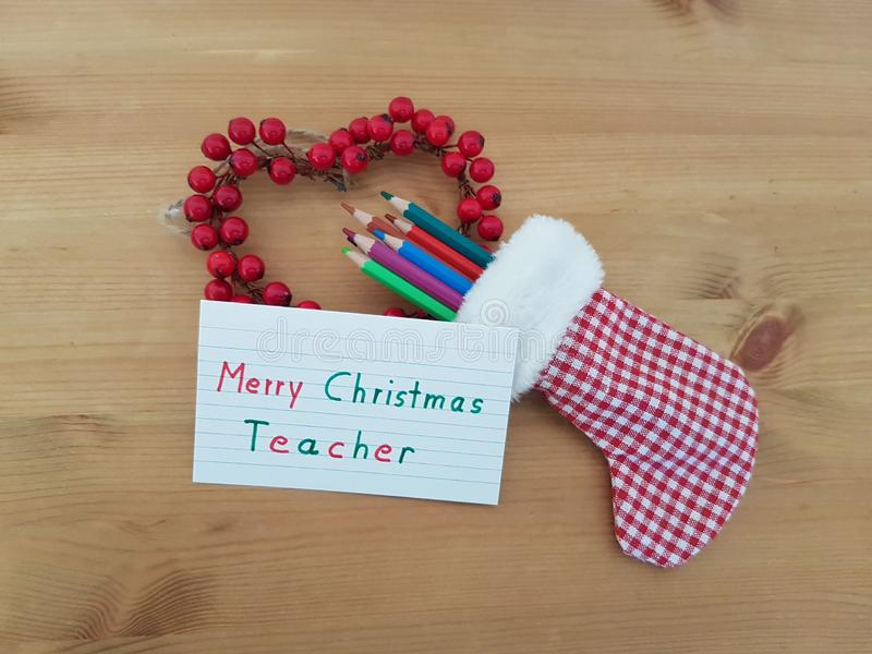 Merry Christmas Note To Teacher With A Christmas Stocking, Colored Pencils And Wreath stock photos