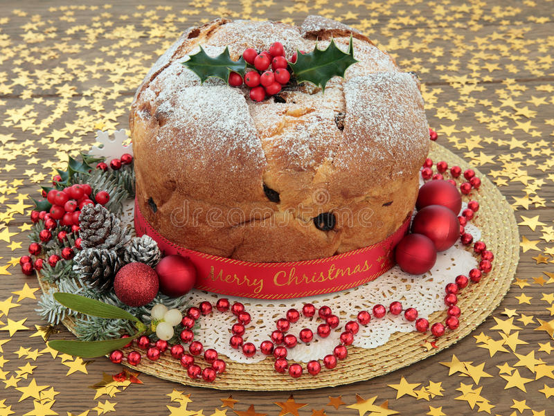 Merry Christmas. Panettone cake with merry christmas ribbon, holly, mistletoe, decorations and winter greenery over oak background with gold stars stock images