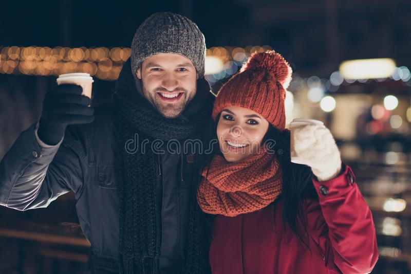 Merry christmas. Photo of two people pair with hot beverage in hands celebrating x-mas evening raising mugs telling royalty free stock image