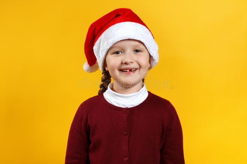 Merry Christmas. Portrait of a cheerful funny baby in Santas hat. Little girl close-up on a yellow background stock images