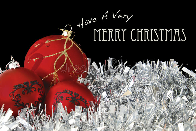 Merry christmas with red baubles on tinsel stock photo