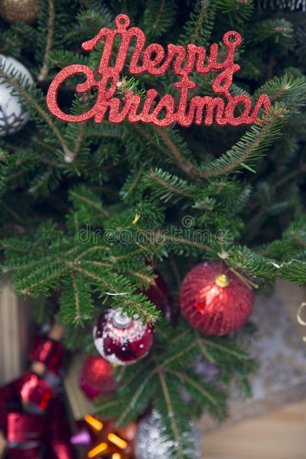 Merry christmas red gleaming inscription on a decorated fir tree stock photography