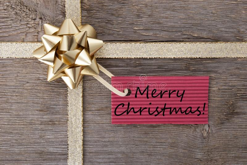 Merry christmas on a red label. On a golden bow, christmas background stock photo