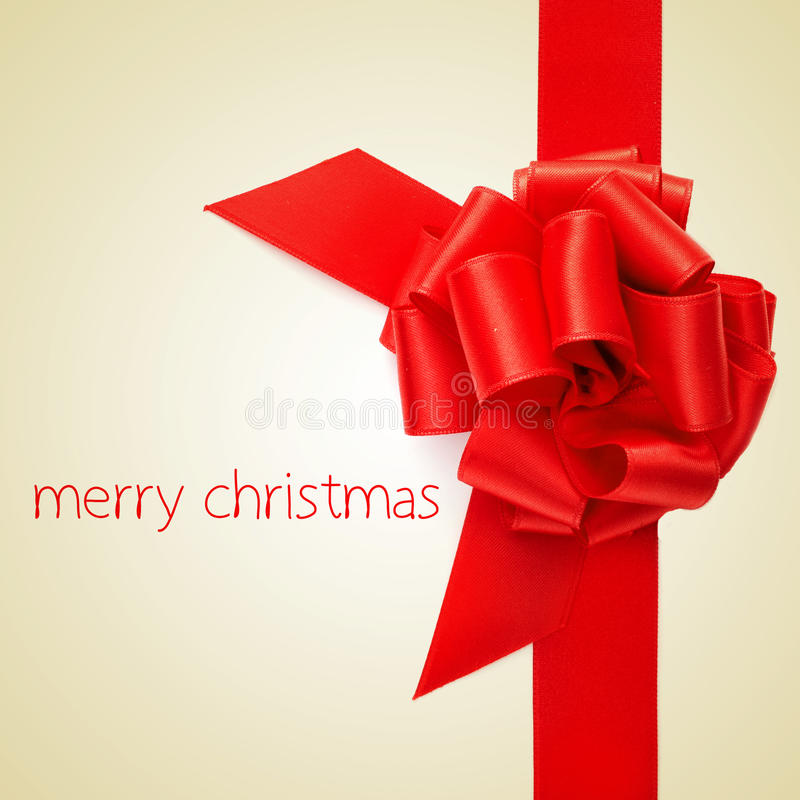 Merry christmas. And a red ribbon bow on a beige background stock photos