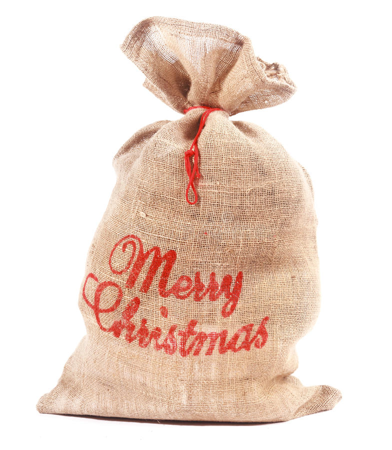 Merry Christmas sack full of gifts. Merry Christmas rustic hessian sack full of gifts with a red Christmas greeting on the side tied with string over a white stock photography