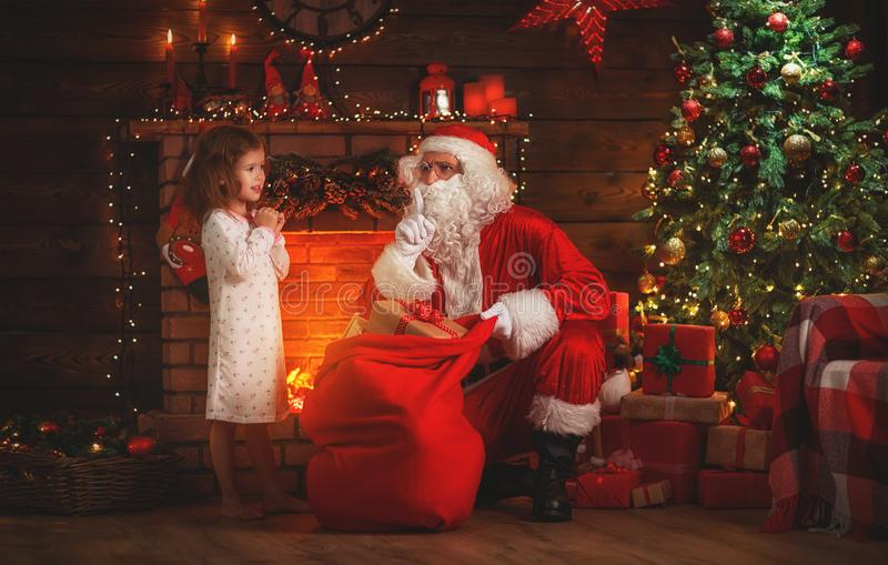 Merry Christmas! santa claus and child girl at night at the Chr. Merry Christmas! santa claus and little child girl at night at the Christmas tree royalty free stock photography