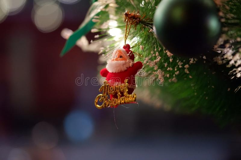 Merry Christmas, with Santa Claus doll blurred Christmas tree background. In Christmas festival. Closeup for Santa Claus doll and blur background royalty free stock image