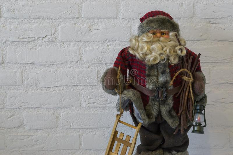 Merry christmas, a santa claus doll in closeup holding a sleigh and lantern isolated on a white brick wall background. A merry christmas, a santa claus doll in stock image