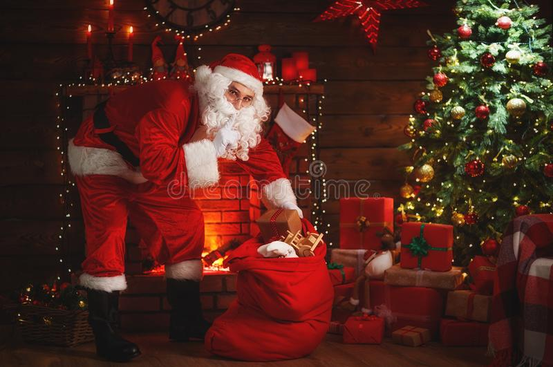 Merry Christmas! santa claus near fireplace and tree with gift stock image