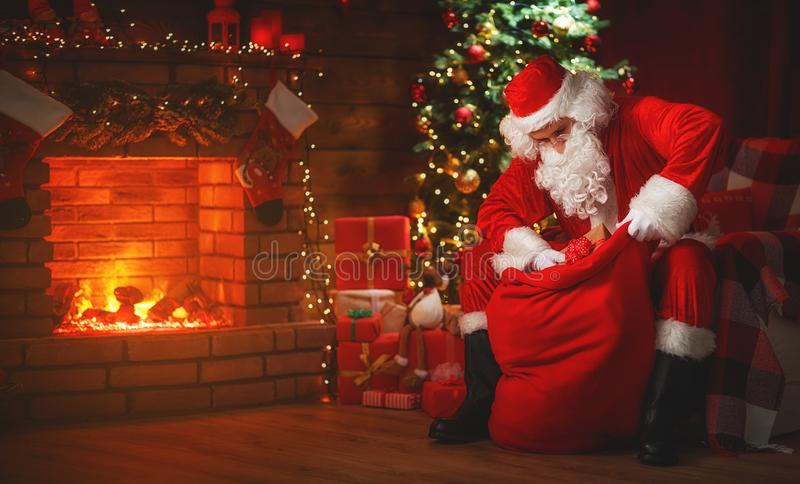 Merry Christmas! santa claus near the fireplace and tree with gi royalty free stock photo