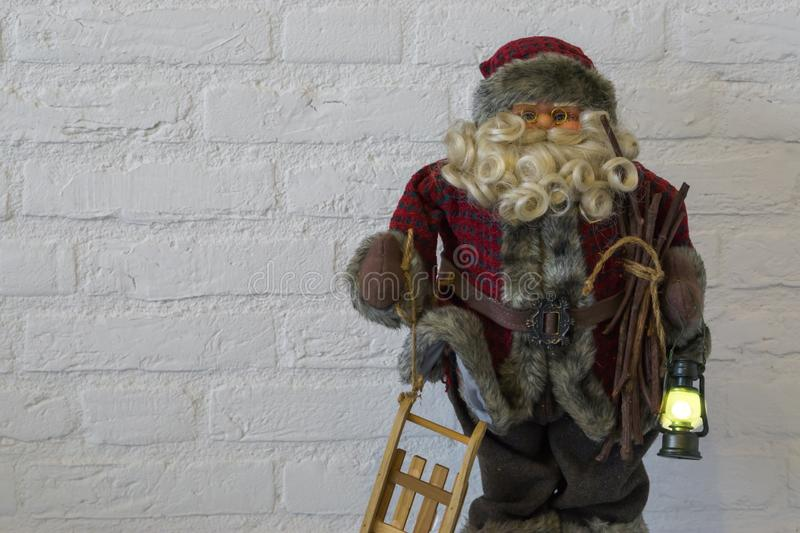 Merry christmas, Santa claus puppet decoration holding a lighted lantern and a sleigh on white brick wall background. A Merry christmas, Santa claus puppet stock image