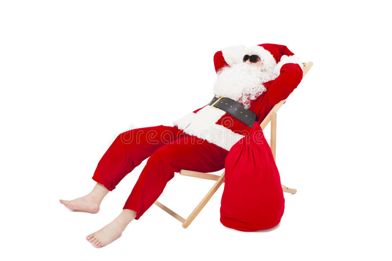 Merry Christmas Santa Claus sitting on a chair with gift bag. Over white background royalty free stock photo