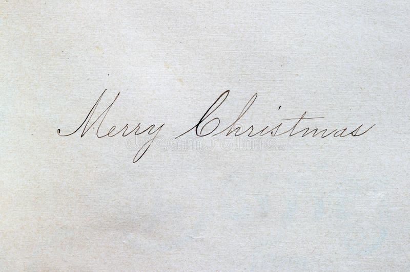 Merry Christmas script. Merry Christmas written in cursive script on paper with an ink pen stock image
