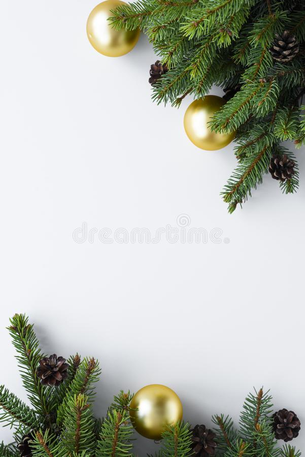 Merry Christmas set up in vertical position, copy space on white background. Conifer tree branches, cones and gold baubles. Merry Christmas set up in vertical royalty free stock photo