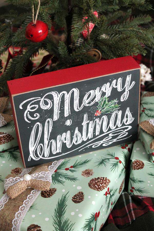 Merry Christmas Sign on Gifts. A Merry Christmas sign on top of a bunch of wrapped gifts stock image