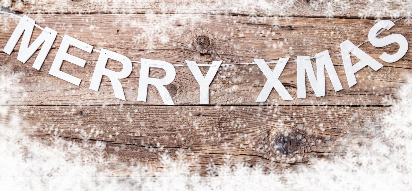 Merry Christmas sign on wooden background with copy space. Merry Christmas sign with snow on wooden background with copy space royalty free stock photos
