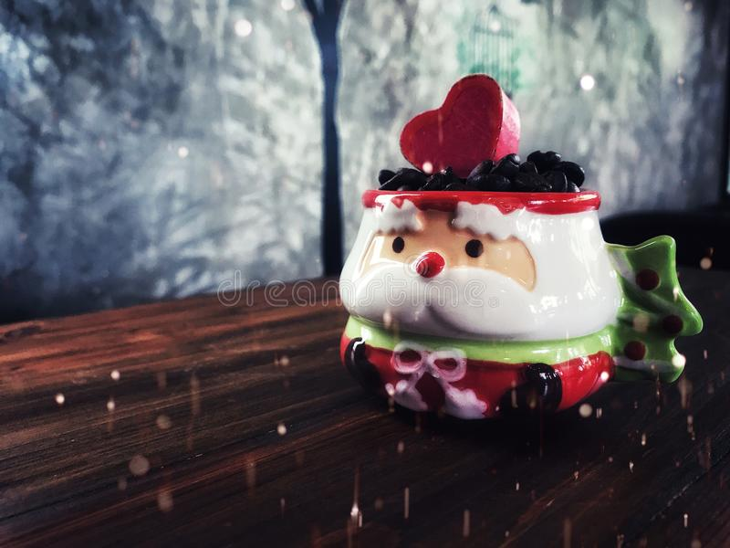 Merry Christmas snow day ,coffee beans in Cute Santa Claus Cup. On the wooden table. vintage style and low light royalty free stock photo