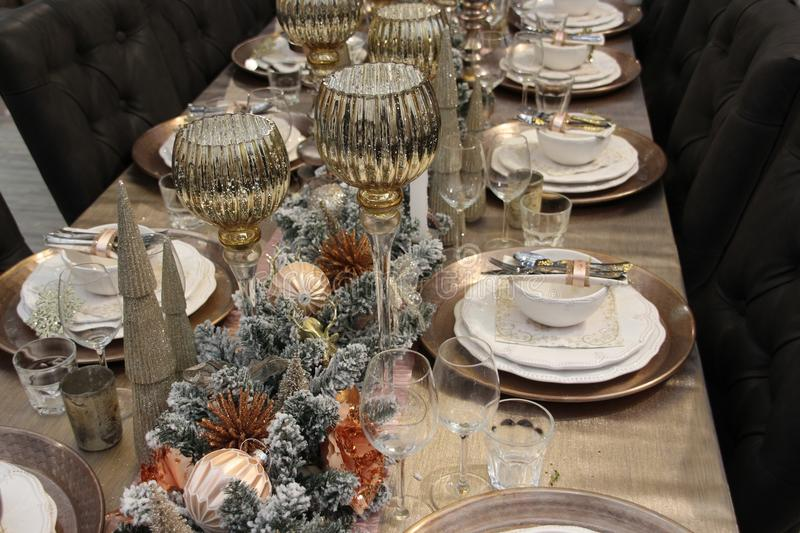 The table is covered, Merry Christmas. Merry Christmas, the table is covered with decoration like candles, baubles and forks, spoons, knives, plates and glasses royalty free stock image