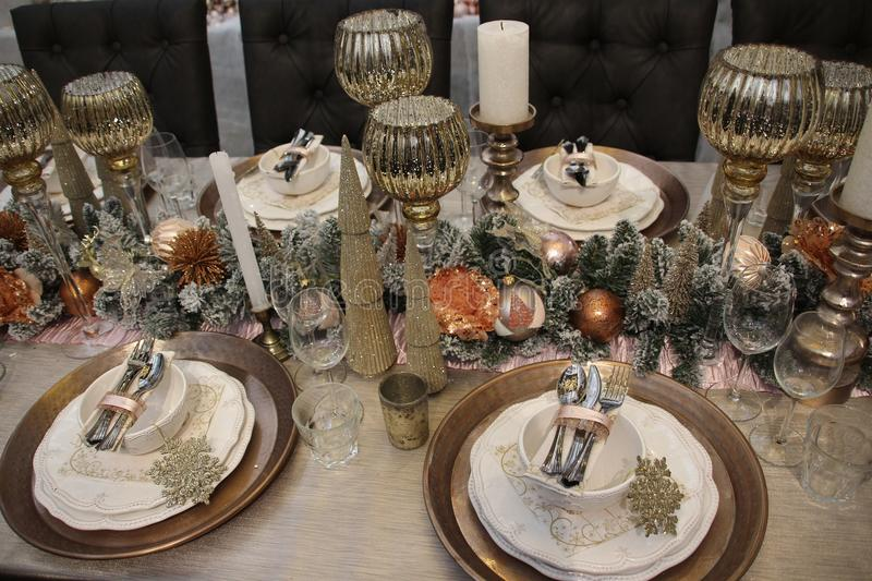 The table is covered, Merry Christmas. Merry Christmas, the table is covered with decoration like candles, baubles and forks, spoons, knives, plates and glasses stock image