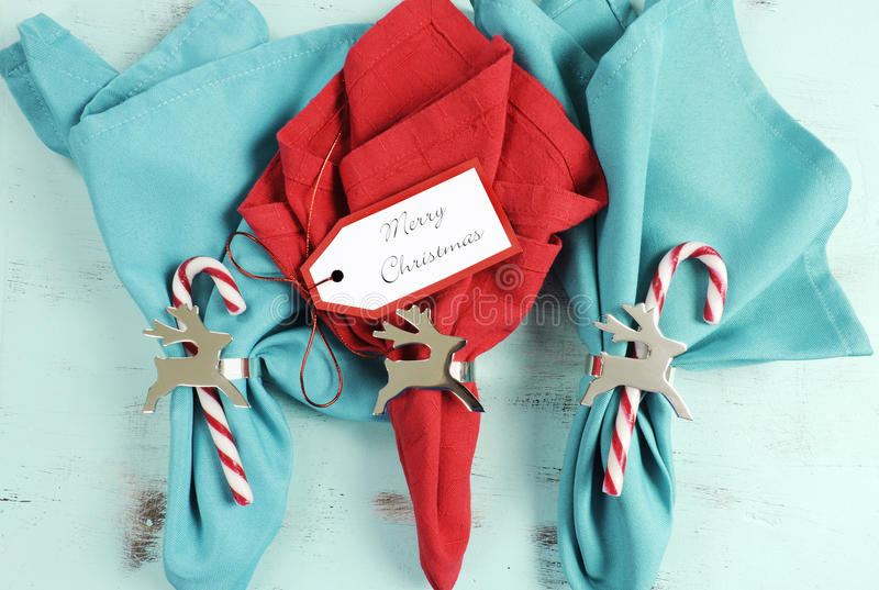 Merry Christmas table place setting red and aqua blue napkins. With silver reindeer napkin holders on vintage shabby chic pale blue table royalty free stock photography