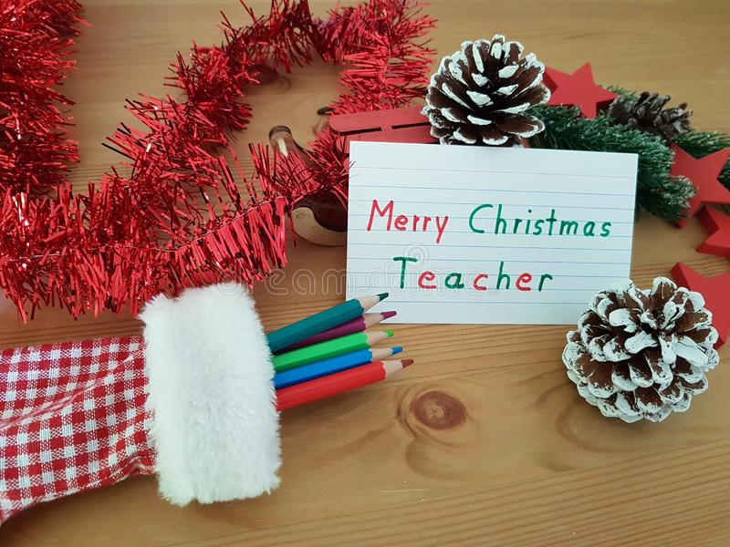 Merry Christmas Teacher, Stocking With Colored Pencils, Pine Cone And Sled stock image