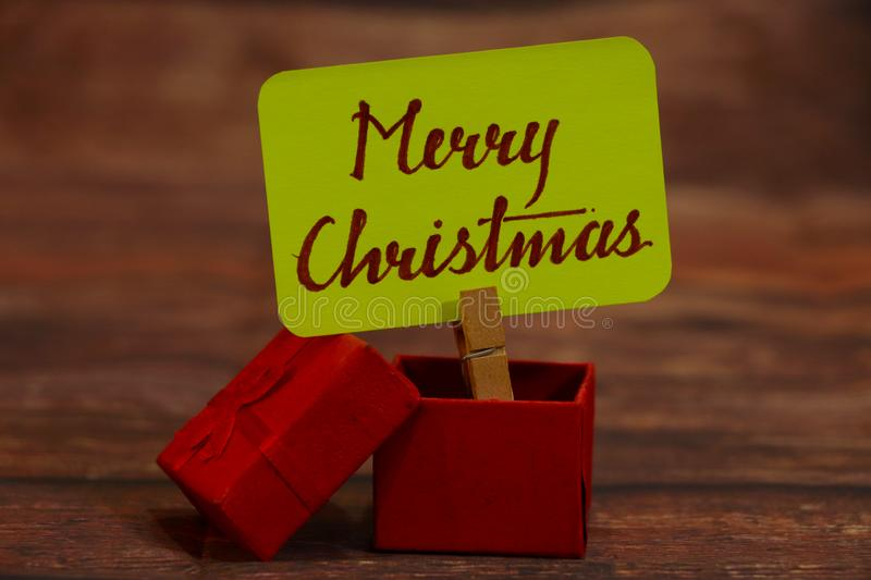 Merry Christmas text with gift box. Merry Christmas text attached with clip with with gift box stock images