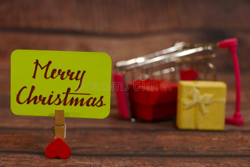 Merry Christmas text with cart full of gifts. Merry Christmas text attached with heart clip with cart full of gifts in the background royalty free stock photos