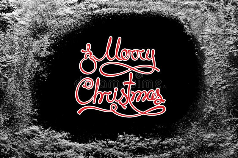 Merry Christmas text on black background and hoarfrost snow frost on xmas window stock images