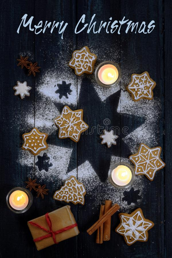 Merry Christmas text greeting card with gingerbread cookies, spices and candles on a star from icing sugar on dark blue wooden. Background, high angle view from stock photo