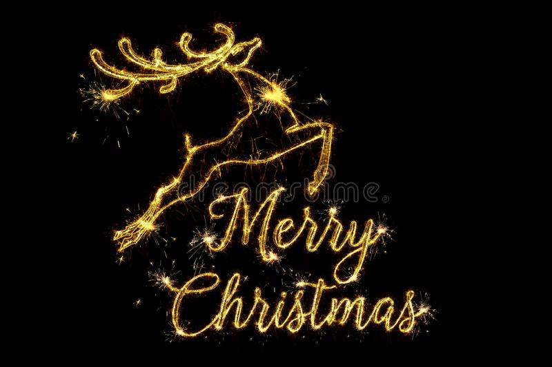 Merry Christmas of 2020. Text Merry Christmas written sparkling sparklers fireworks and silhouette of the jumping deer isolated on. Black background. Overlay royalty free stock photography